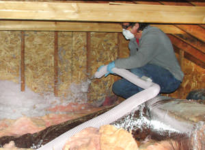 an HVAC expert installing attic insulation in a home in Danbury